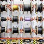 Mehrere verschiedene Kabelrollen mit Kabeln neben- und übereinander an einer Stahlkonstruktion angebracht