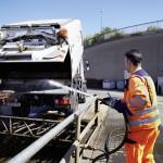 Mann spritzt Ladefläche des Schienenreinigungsfahrzeug ab
