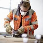 Mann in orangener Arbeitskleidung mit Baukopfhörer, Maske und Schutzbrille schleift Metallstück.