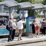 """Personen laufen an der Haltestelle """"Festhalle/Messe"""" bei sonnigem Wetter entlang"""