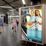 Plakate um eine Säule und verschwommene Personen beim Gehen in der B-Ebene einer Haltestelle