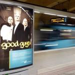 """""""Good Guys"""" Plakat an einer unterirdischen Haltestelle. Im Hintergrund eine Frau vor einer vorbeifahrenden U-Bahn"""