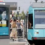 """Plakat """"Die Akte Ivankovic"""" vor einer Straßenbahnhaltestelle an der Personen in die Straßenbahn 11 einsteigen wollen."""