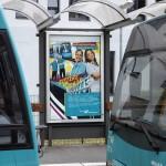 """Plakat """"Sisters on Rails"""" am Haltestellen-Häuschen zwischen zwei Wagons zu sehen"""