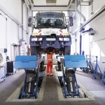 Mitarbeiter in orangener Arbeitskleidung unter VGF Fahrzeug, das auf Wagenhebern steht, in der Werkstatt