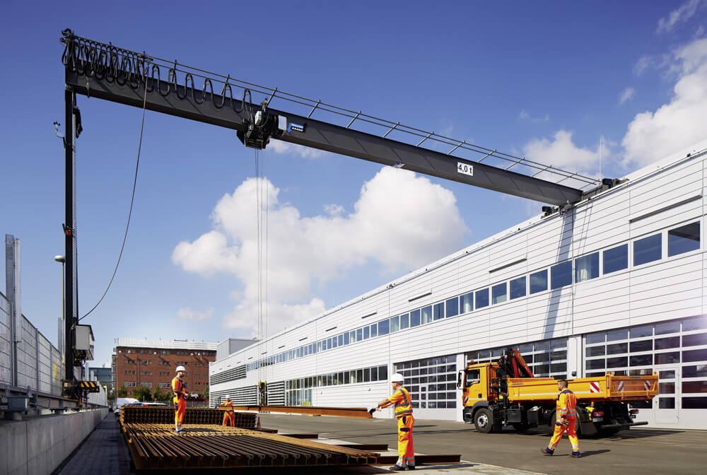Bauarbeiter stapeln lange Eisenstangen mithilfe eines Krans