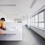 Bauarbeiter wäscht sich am Waschbecken im Gemeinschaftsbad die Hände