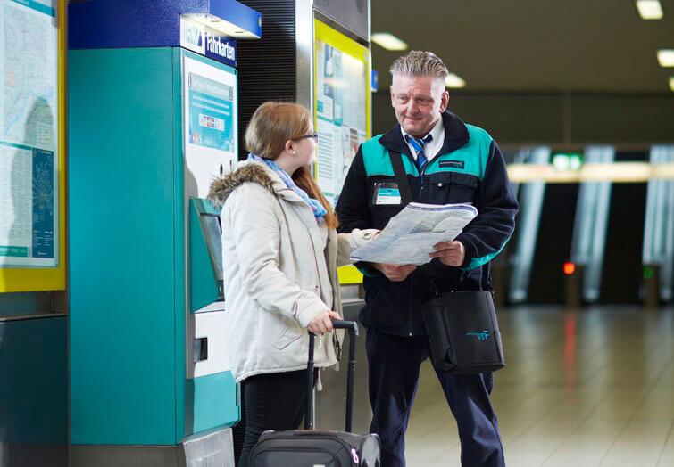 Mitarbeiter der VGF steht mit junger Frau vor einem Fahrkartenautomaten und hält einen Linienfahrplan in der Hand