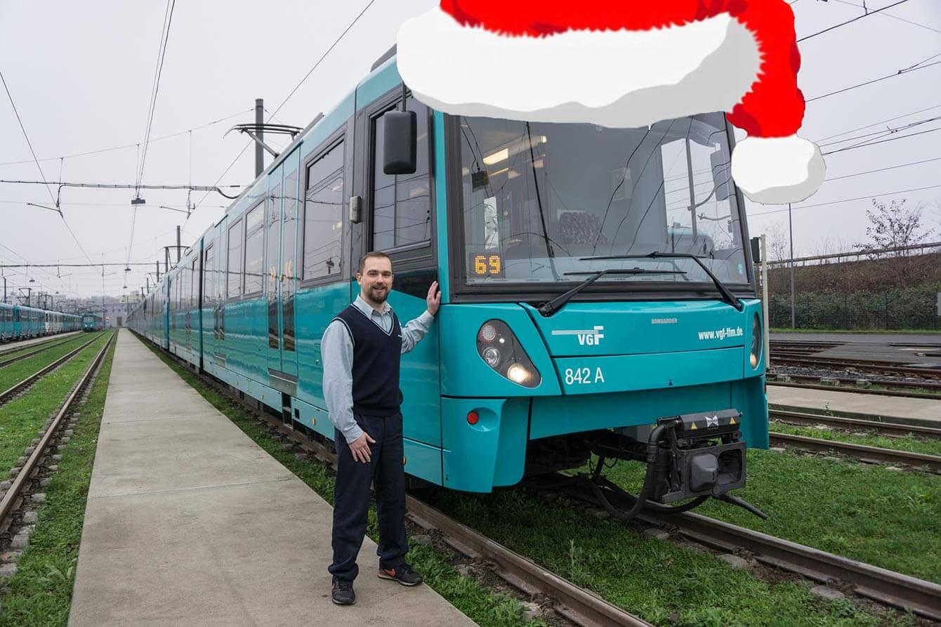 Mitarbeiter der VGF neben einer VGF Bahn auf die eine Weihnachtsmütze editiert wurde.