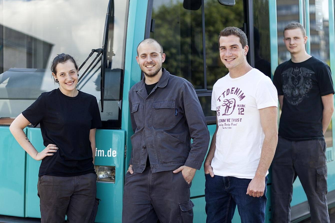 Vier Junge Menschen vor einer VGF Bahn lächeln in die Kamera