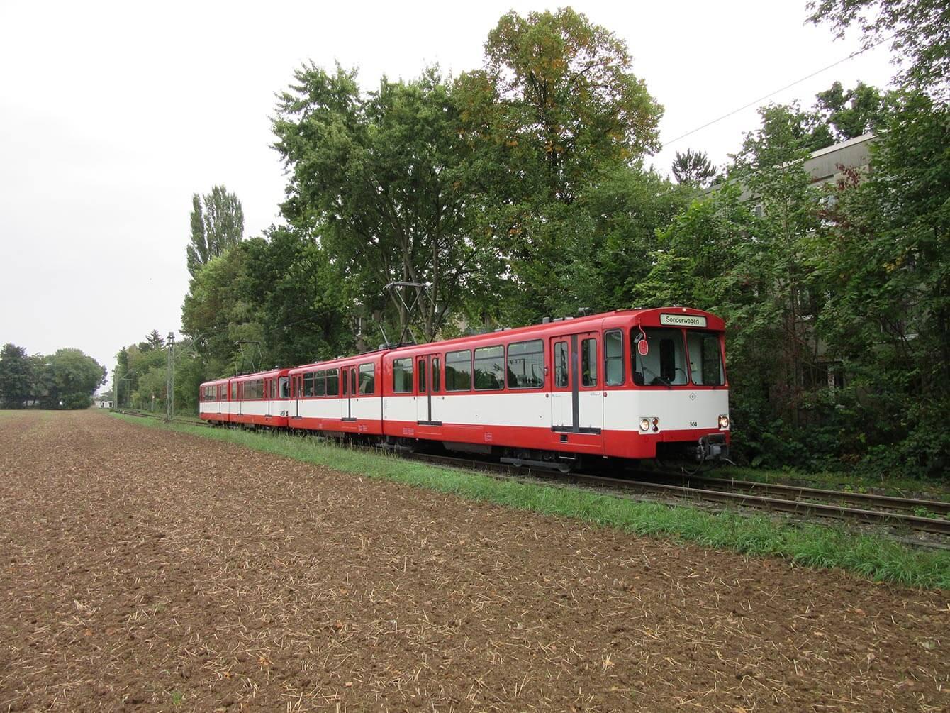 Sonderfahrt Rot-weiß Bahn auf einer Strecke vorbei am Acker und Bäumen