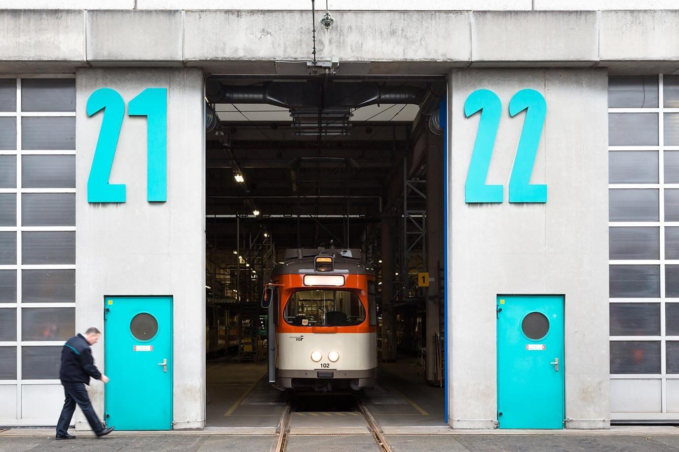 Halle mit großen VGF-grünen Zahlen 21 und 22 auf der Fassade, darunter in der selben Farbe jeweils eine Tür und dazwischen eine Oldtimer-Bahn