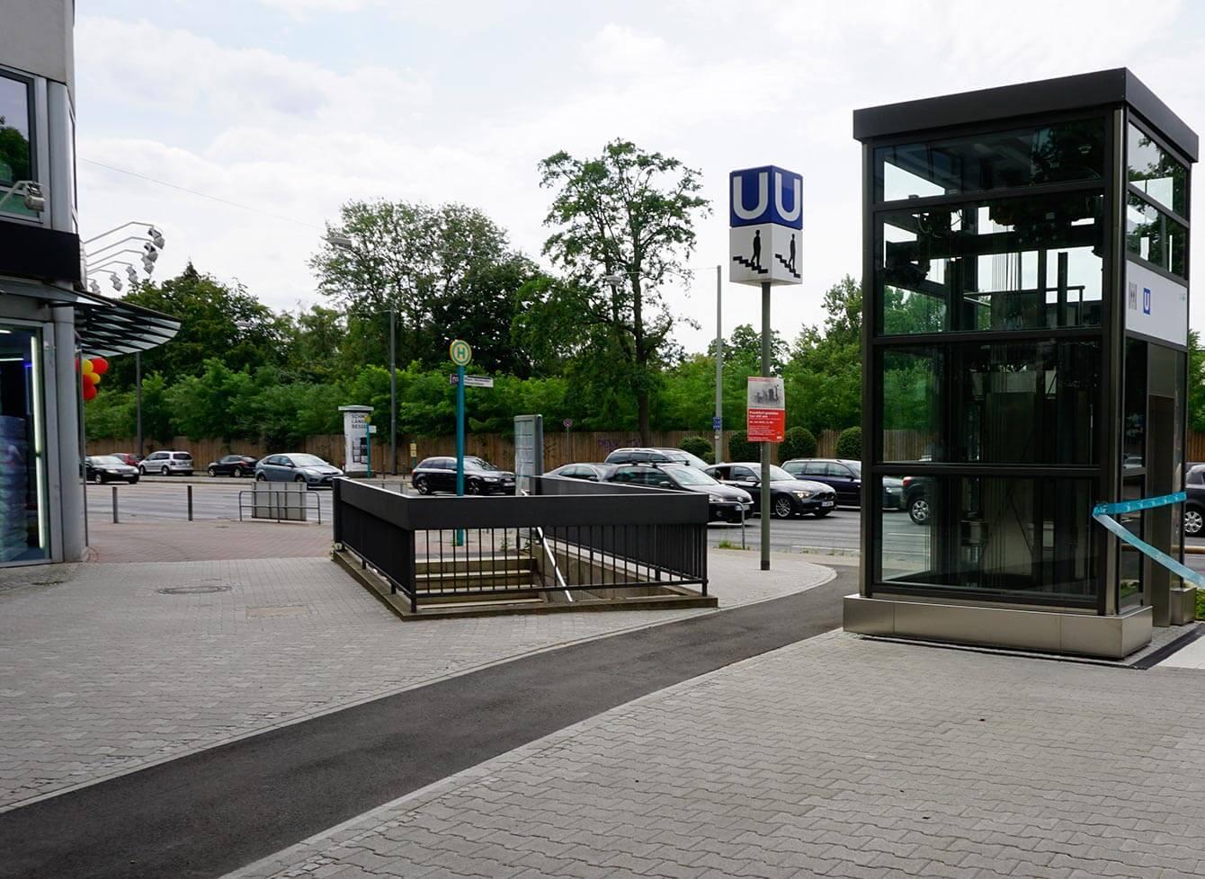 """Verglaste Aufzugsanlage Miquel-/Adickesallee von außen am Eröffnungstag. Daneben die Treppe zur unterirdischen Haltestelle, ein blaues Schild mit einem """"U"""" darauf und darunter ein weißes mit einer Person die die Treppe herunter läuft."""
