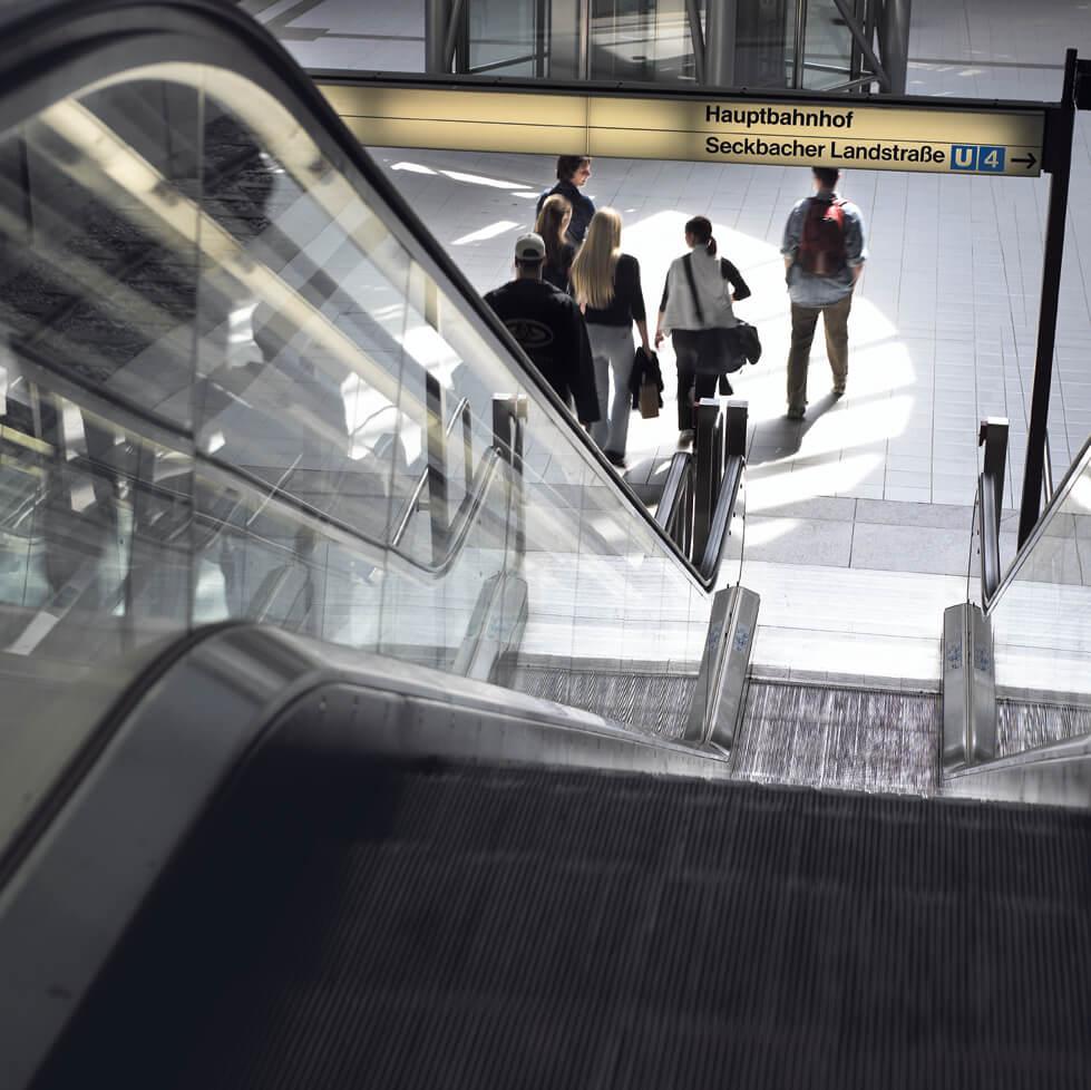 Rolltreppen von oben nach unten fotografiert. Unten laufen sechs Personen die unterirdische Haltestellen-Plattform