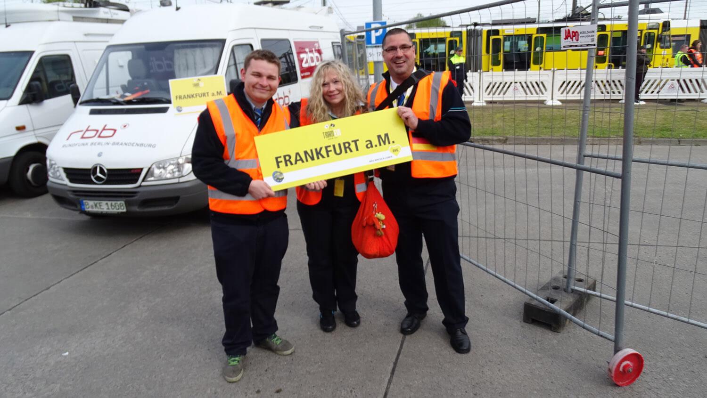 """Drei Mitarbeiter der VGF tragen orangene Warnwesten und halten ein gelbes Schild """"Frankfurt a.M."""""""