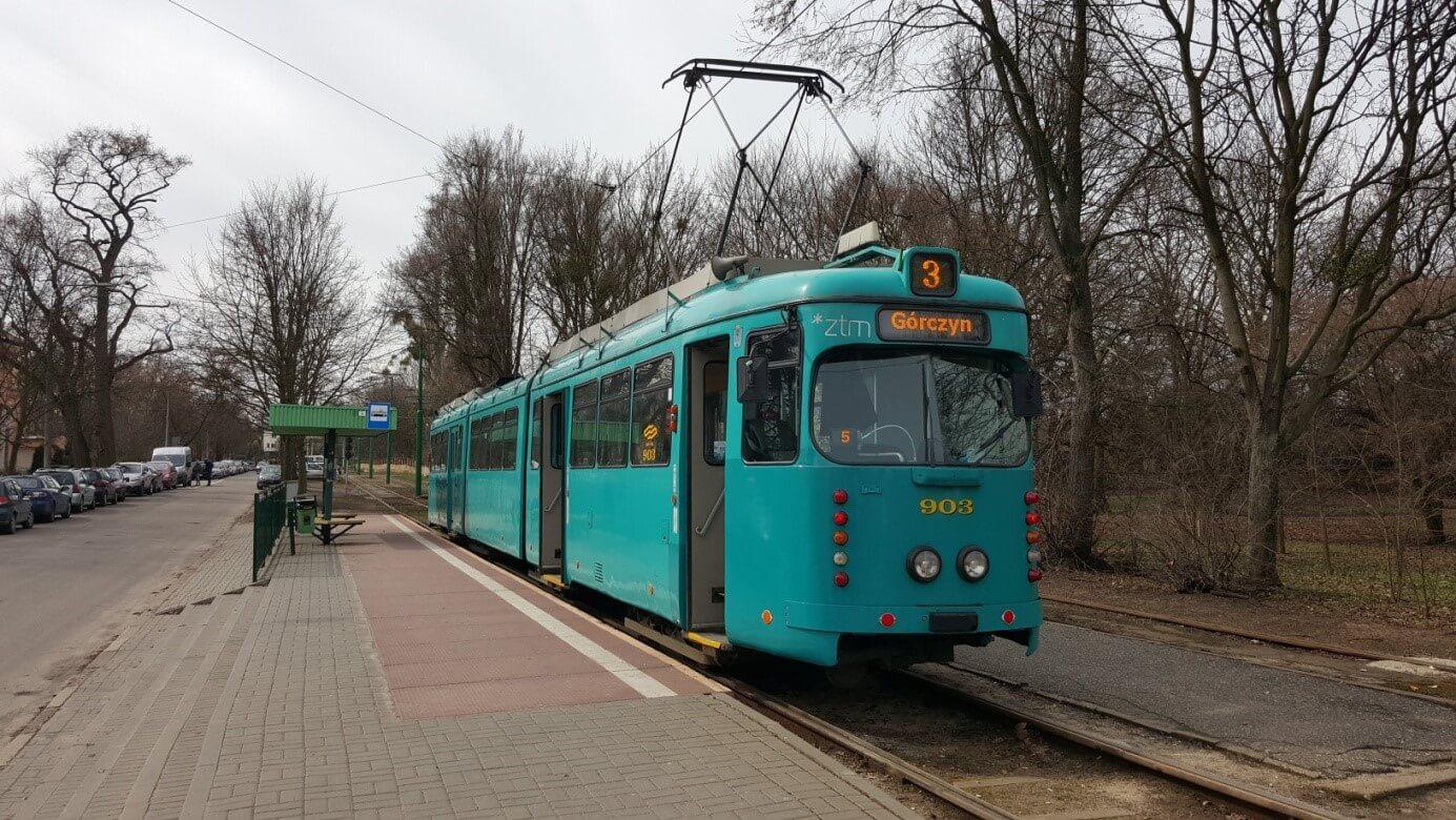 """O-Wagen in """"subaru-vista-blue""""-Lackierung in """"Wilczak"""" an einer Haltestelle."""