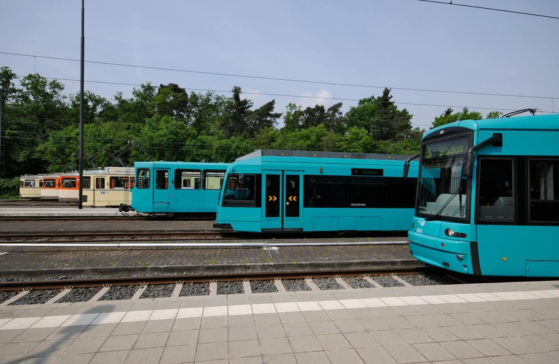 Sieben Straßenbahnen versetzt hintereinander auf den Gleisen stehend von alt (hinten) bis neu (vorne)