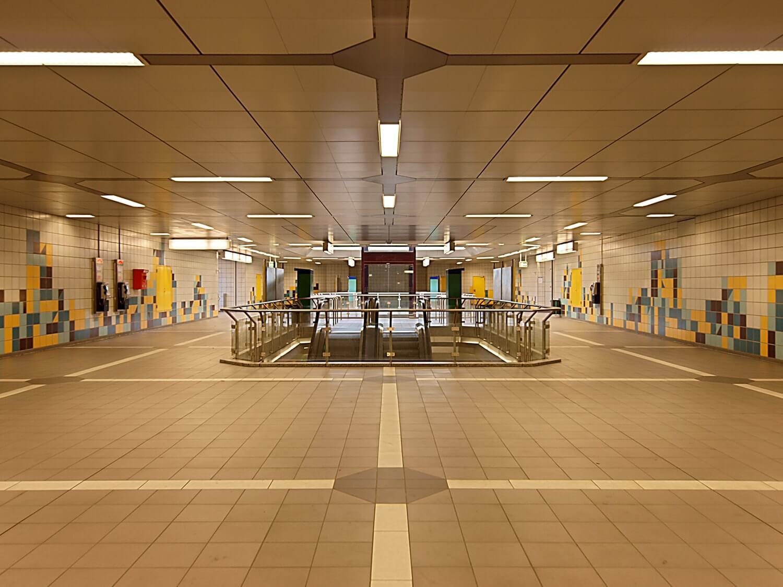 Komplett gefliester Gang der B-Ebene des Ostbahnhofs. Mitte die Treppe und Fahrtreppe, dahinter der Aufzug.