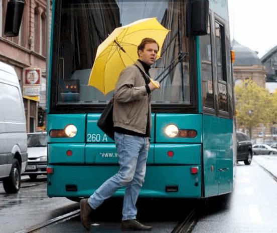 Mann mit gelben Regenschirm läuft vor einer Bahn über die Straße