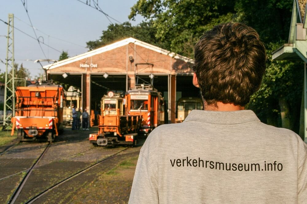 """Person von hinten mit grauem Shirt mit Aufschrift auf dem Rücken """"verkehrsmuseum.info"""" vor der Halle Ost mit Schienenbaustellenfahrzeugen."""