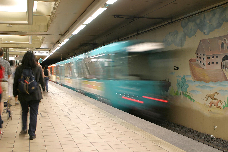 Bahn bei der Einfahrt an der unterirdischen Haltestelle an der Passanten auf dem Bahnsteig laufen.