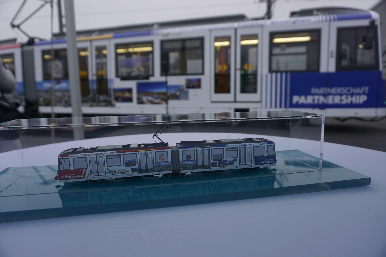 Bahn Modell in einem Glasgehäuse auf einem Tisch vor einer Bahn