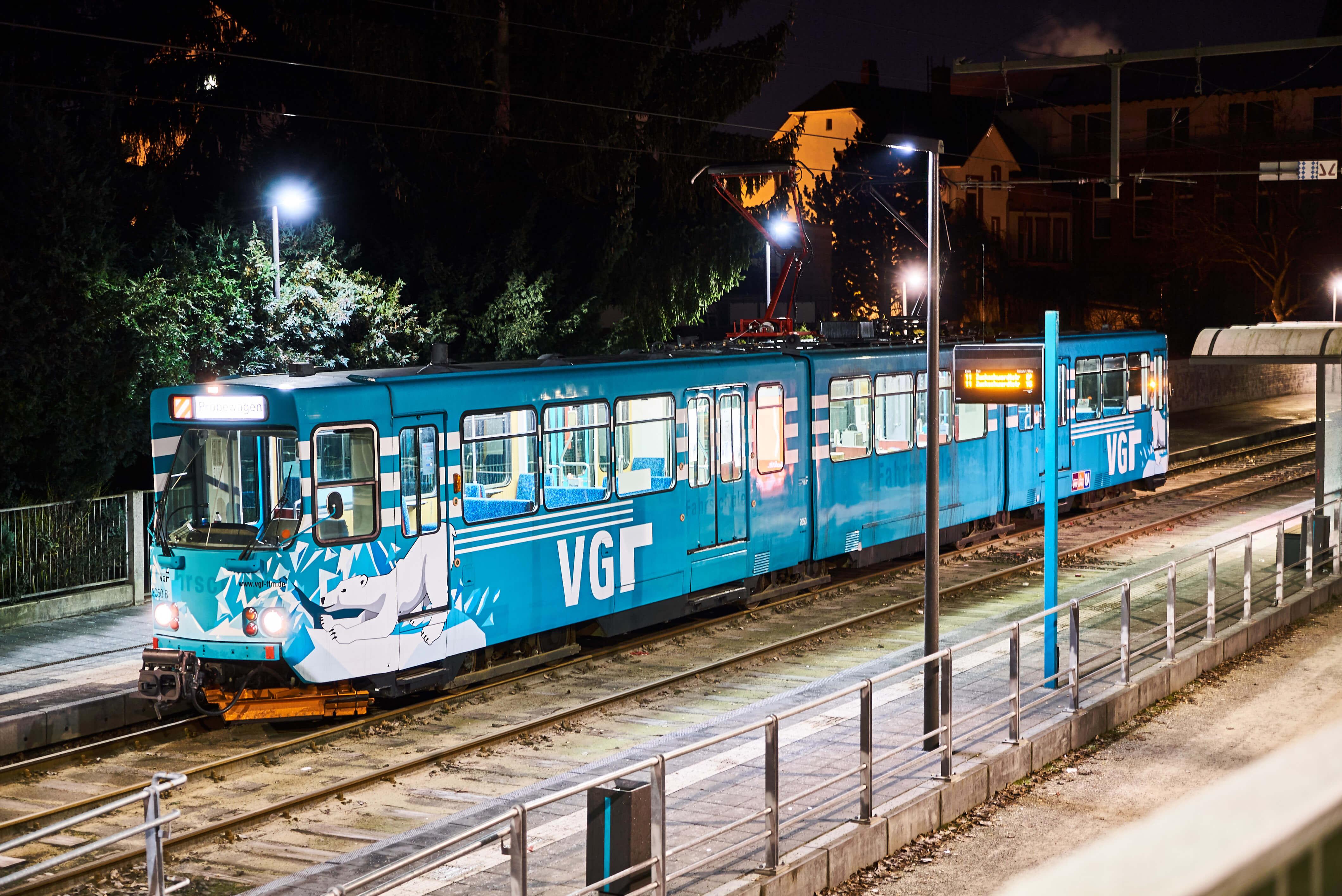 Schneeschieber-Bahn am einer Haltestelle bei Nacht.