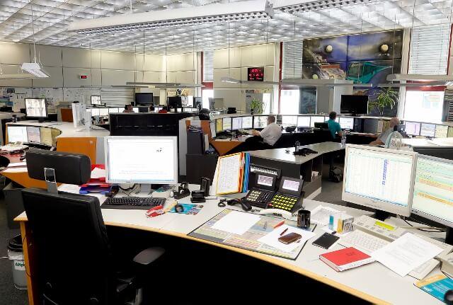 Großraumbüro der Betriebsleitstelle mit vielen Bildschirmen, Telefonen und Unterlagen.