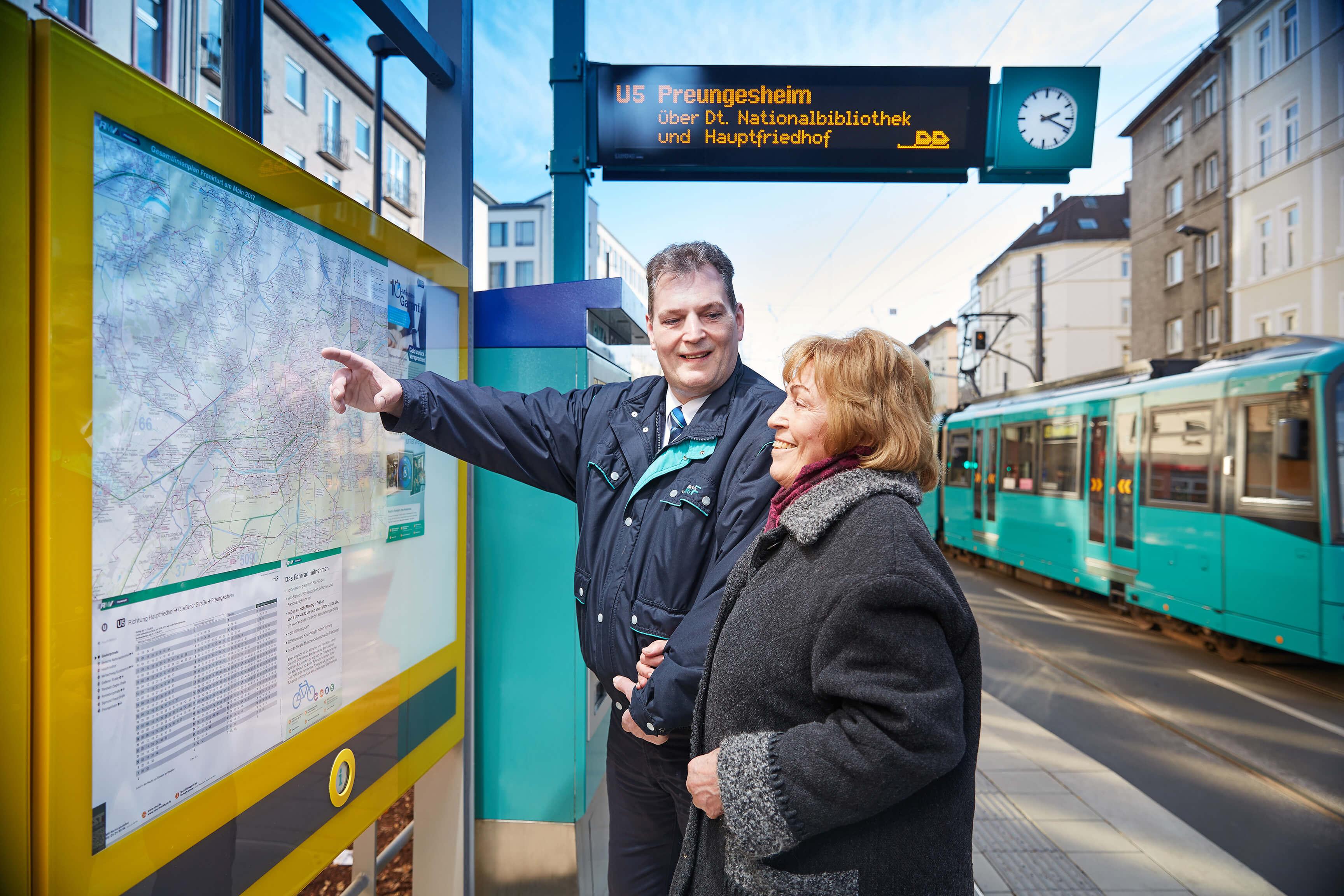 Mitarbeiter der VGF zeigt Dame den Fahrplan-Aushang am Bahnsteig.