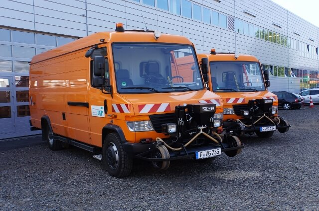 Zwei orangene Zweiwegefahrzeuge vor einem Gebäude die auf Straße und Schienen fahren können.