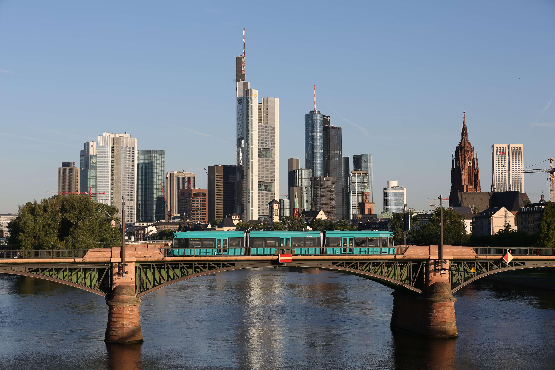 Skyline Frankfurt mit dem Main davor und einer Bahnbrücke auf der eine VGF-bahn fährt.