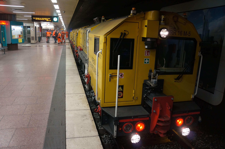 Schienenschleiffahrzeug an einer unterirdischen Haltestelle an der Personen in orangener Arbeitskleidung stehen.