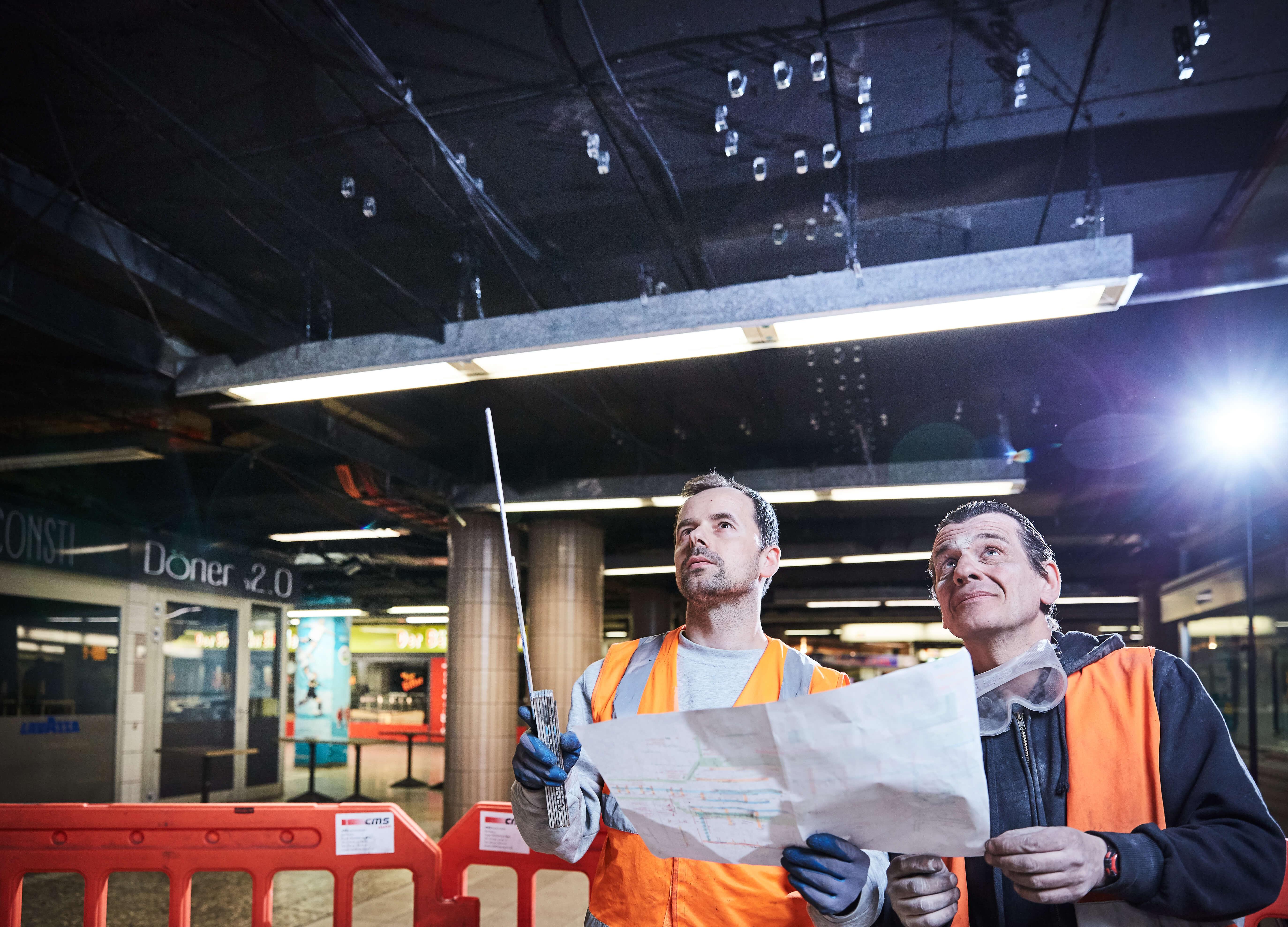Zwei Männer in Warnwesten Metermaß und Plan in der Hand schauen an die Decke der B-Ebene