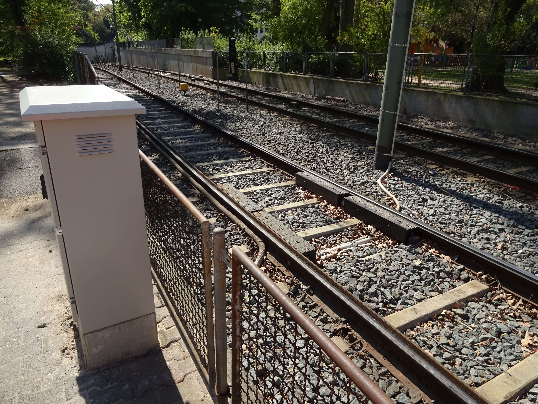 Schienen zwischen Zäunen und begrünter Umgebung und Stromkasten daneben.