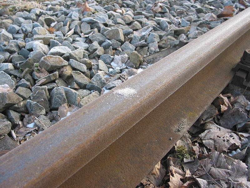 Nahaufnahme einer Schiene auf Schotter