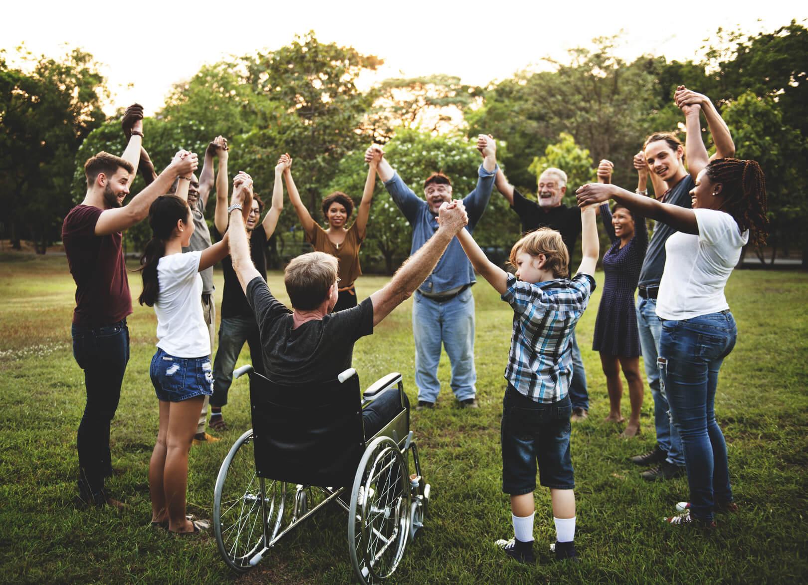 Verschiedene Personen im Kreis auf einer Wiese Hand in Hand halten ihre Arme in die Höhe.