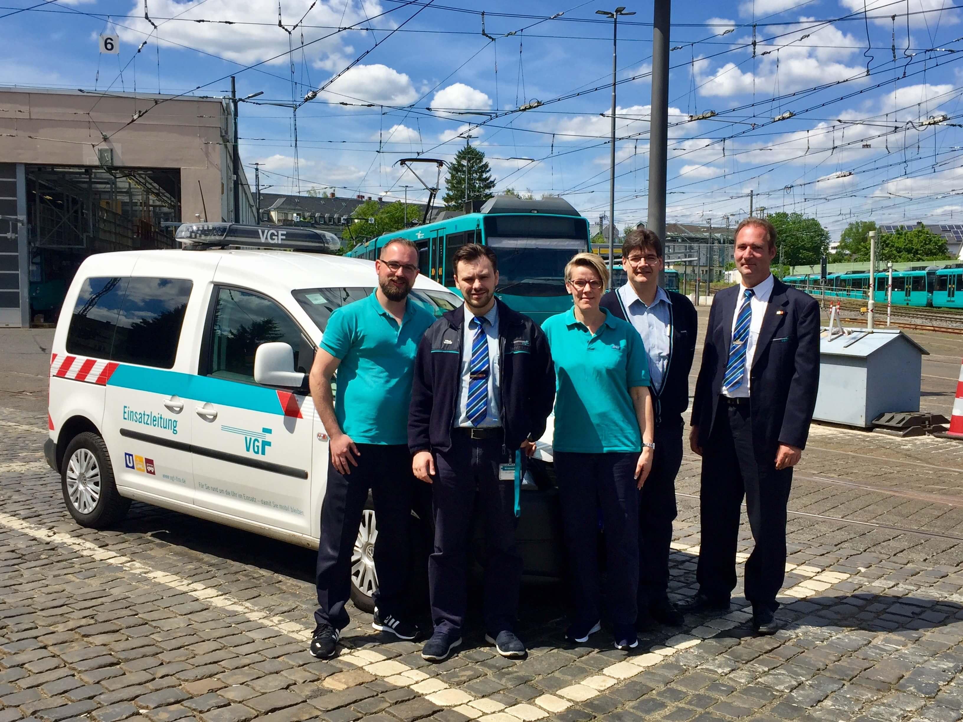Fünf Mitarbeiter der VGF vor dem Auto der Einsatzleitung