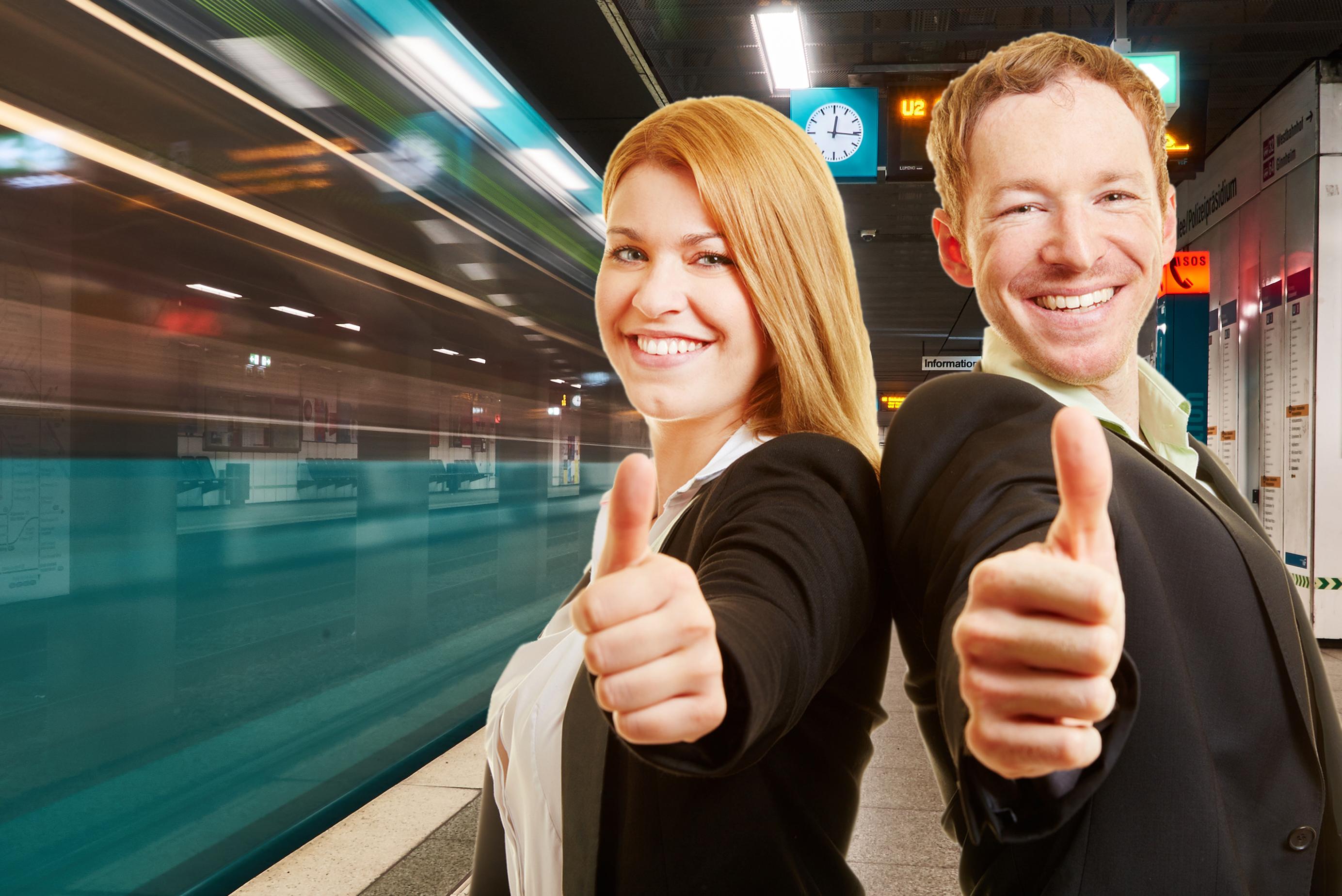 Eine Frau und ein Mann stehen Rücken an Rücken und strecken beide einen Daumen hoch in Richtung Kamera.