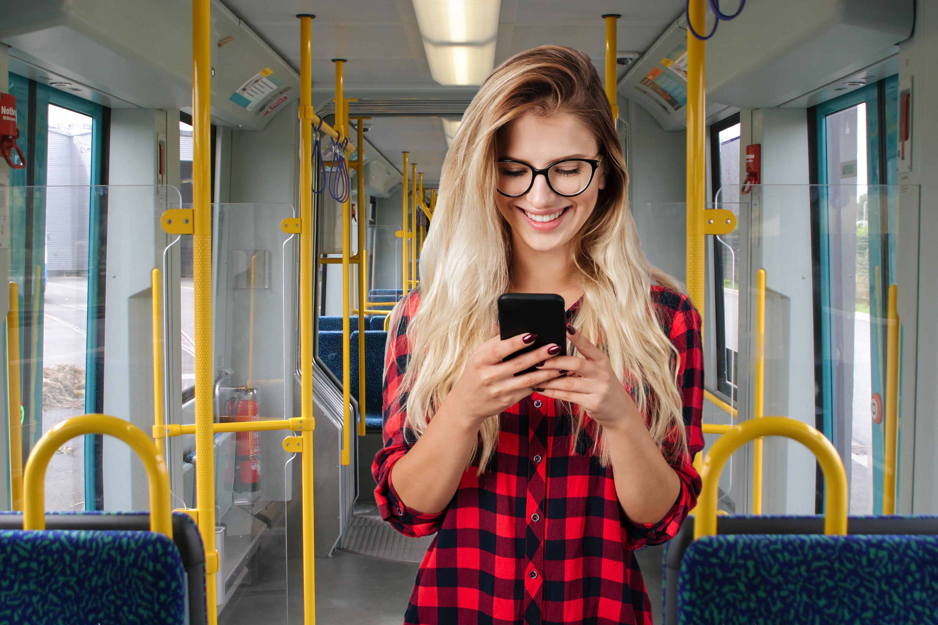 Junge Frau schaut lächelnd auf ihr Handy in der Bahn.