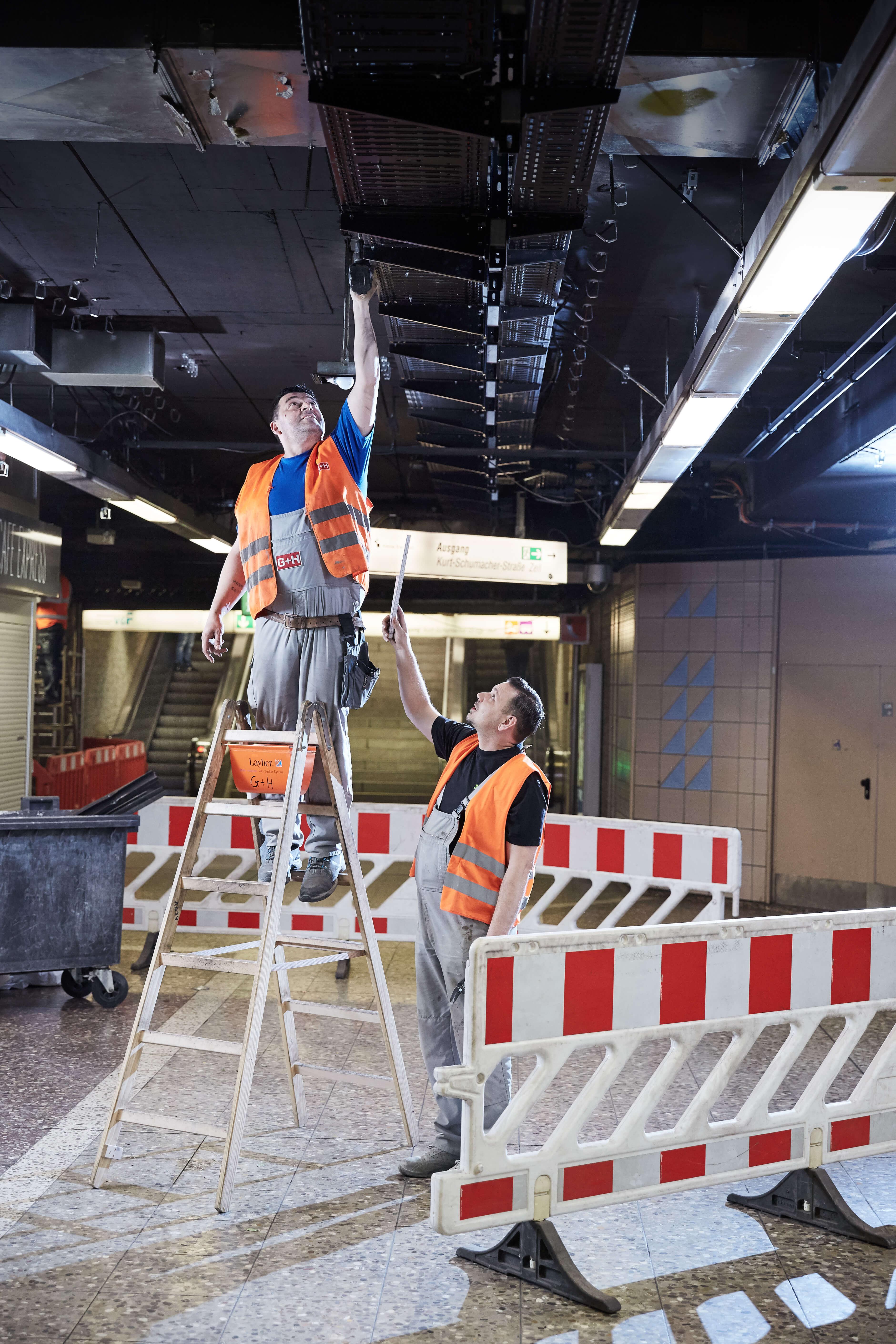 Zwei Männer in Warnwesten, der eine auf einer Leiter mit Akkuschrauber in der Hand, der andere daneben reicht Metermaß an und schaut zu.