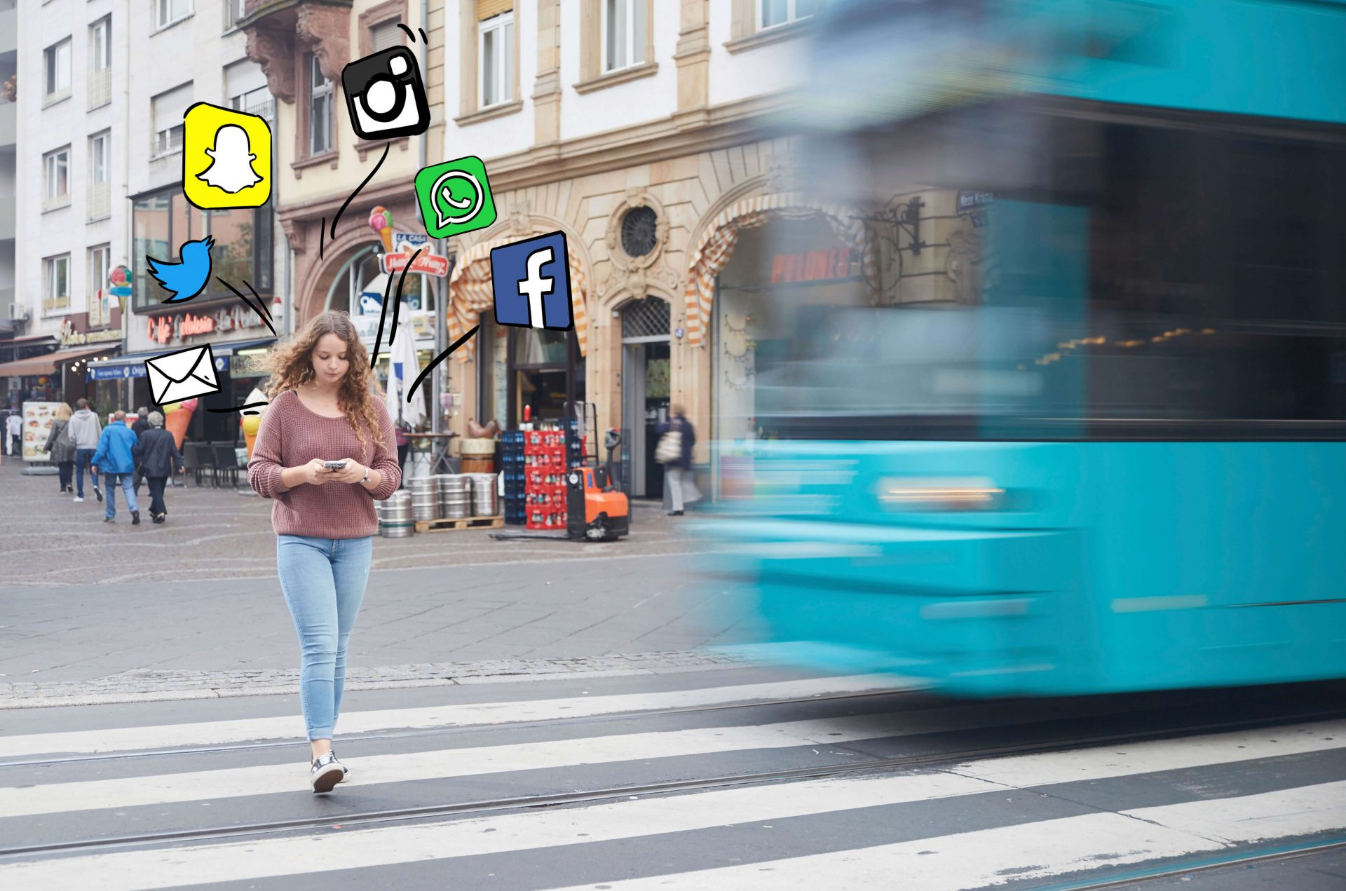Junge Frau schaut beim Überqueren der Schienen über einen Zebrastreifen auf ihr Handy, um sie herum sind Social Media Icons gemalt, während die Bahn näher kommt.