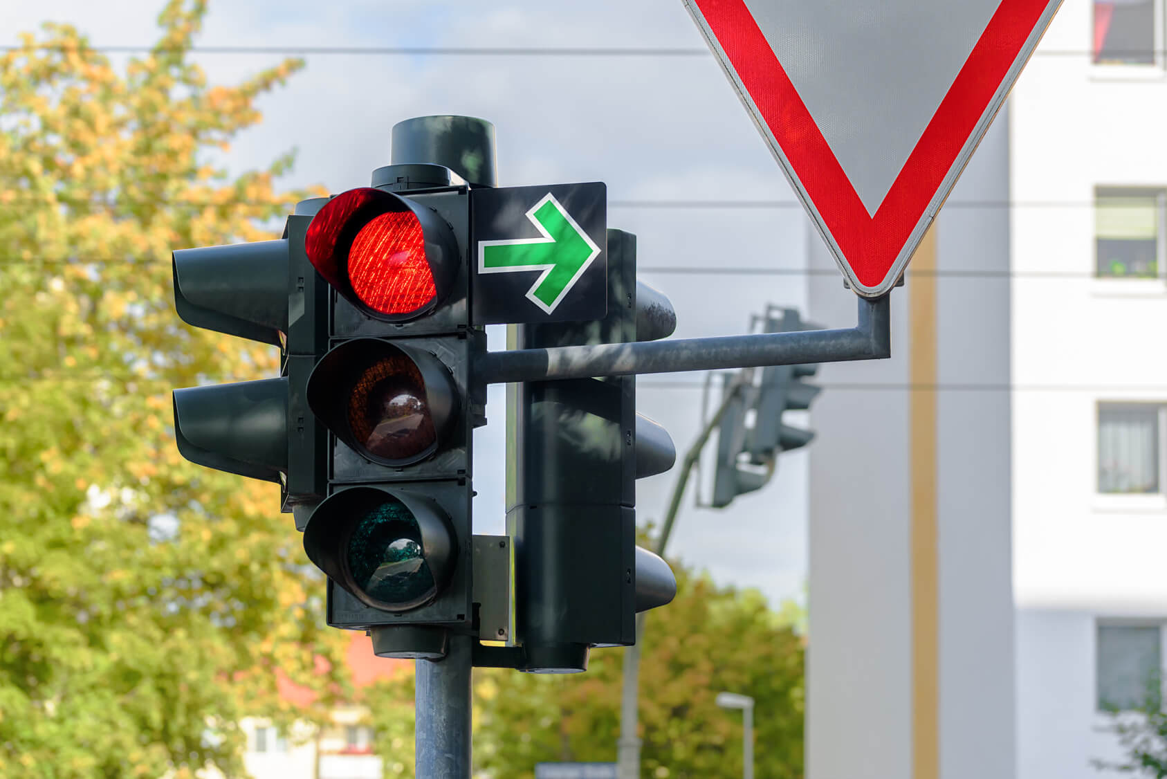 Rote Ampel mit grünem Pfeil nach rechts und einem Vorfahrt-Achten-Schild
