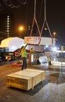 Bauarbeiter nehmen vom Kran angelieferte Rolltreppensegmente in Empfang