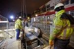 Zwei Bauarbeiter passen das neue Rolltreppensegment im Stationszugang ein.