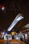 Das neue Rolltreppensegment wird vom Kran an die richtige Position gehoben und schwebt hoch in der Luft ( Ansicht von unten).