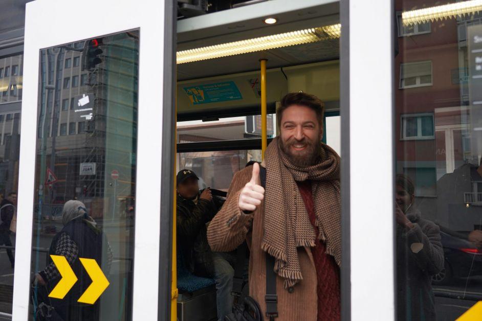 Ferhat, ein Mann, steht mit Daumen hoch in der Straßenbahn