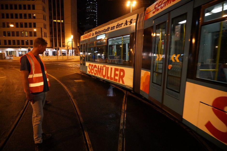 Bauarbeiter betrachtet Straßenbahn bei Nacht